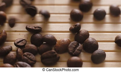 Roasted coffee beans falling on the on the table surface