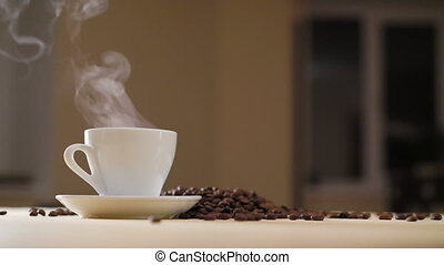 A white cup of evaporating coffee on the table with roasted...