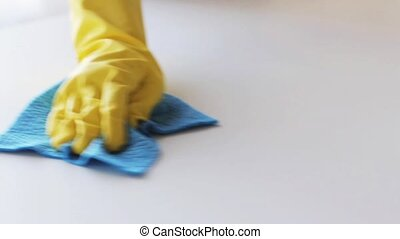 hand in rubber glove with rag cleaning table - people,...