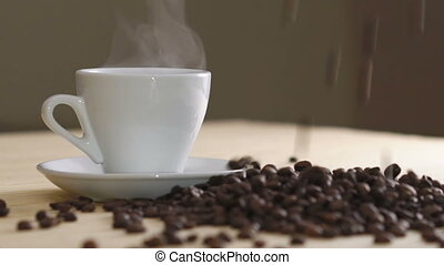 Close up of white cup of evaporating coffee on table near roasted beans. Slowly