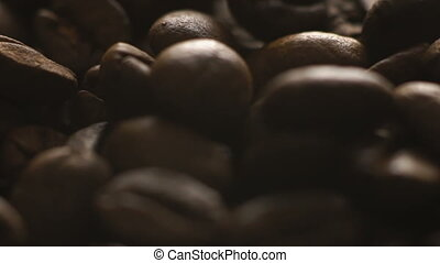 Roasted coffee beans falling on the upside. Slowly.