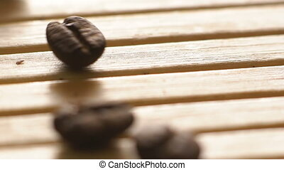 Macro roasted coffee beans falling on the wooden upside....