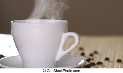 Close up of a white cup of evaporating coffee on table near...