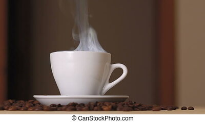 Close up of white cup of evaporating coffee on table near...