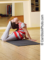 Little gymnast raising feet to head - Little gymnast girl...