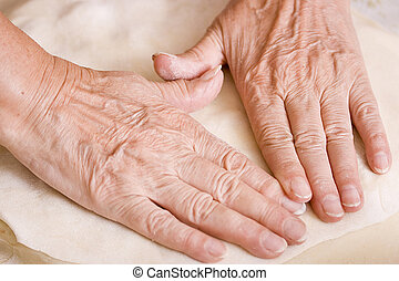 Woman cooking - Hands of an old woman on flattened dough.