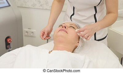 picture of pretty beautician doing rf-lifting procedure for...