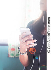 Female listening to music by earphone with smartphone in hand. Copy space