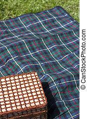 Picnic basket on blanket - Picnic basket on plaid blanket on...