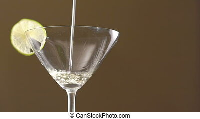 Pouring tequila in the goblet with slice of lime on the...
