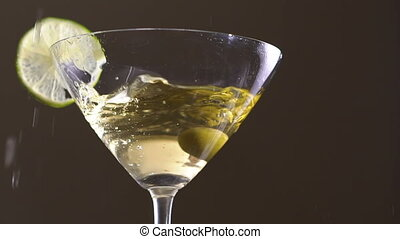 An olive falling into the goblet with the alcohol and slice of the lime. Slowly