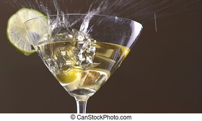 An olive falling into the goblet with the alcohol and slice...