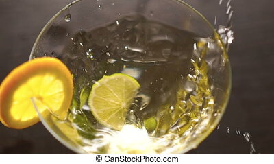A slice of lime falling into goblet with alcohol and slice...