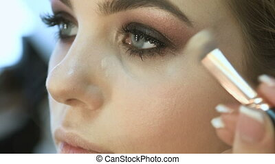 Make-up artist applying eyelash makeup to model's eye. Close up Slow Motion