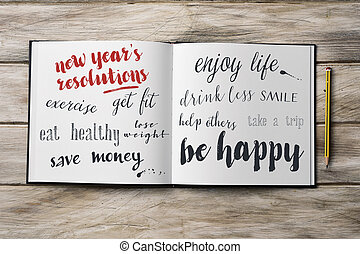 some new years resolutions in a notebook - high-angle shot...