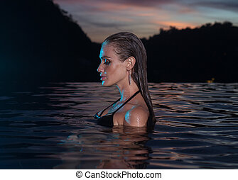Beautiful sensual woman alone in infinity swimming pool -...