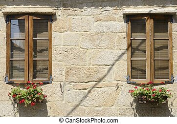 Red flowers pots under wooden windows in Cambados, in...