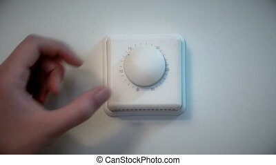 Man adjusting an indoor wall thermostat. - Close-up of a man...