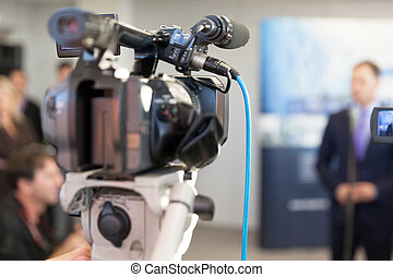 Video camera in focus, blurred spokesperson in background -...