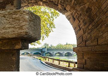 Beziers street alongside Orb River framed by stone bridge...
