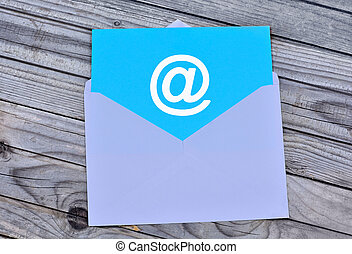 Email symbol in white envelope on wooden table