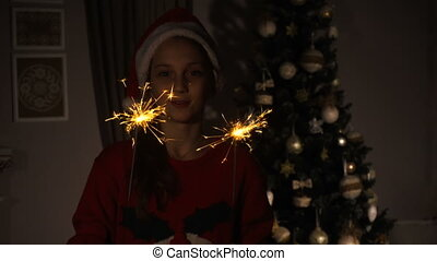 Teen girl with bengal sparkles near christmas tree at home