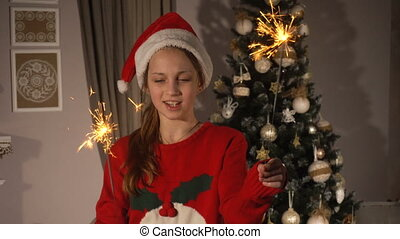 Happy teen girl with bengal sparkles near christmas tree at...