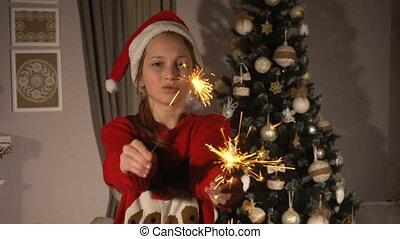 Teen girl with bengal sparkles fireworks near christmas tree...