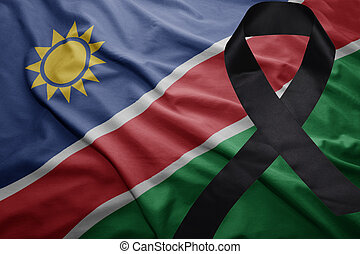 flag of namibia with black mourning ribbon - waving national...