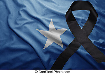 flag of somalia with black mourning ribbon - waving national...
