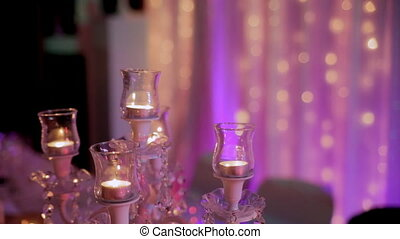 Candelabra with lighted candles in the evening in the hall.