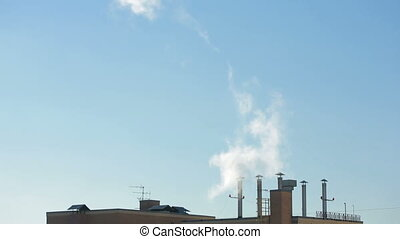 smoke from the chimneys of town houses on a background of blue sky