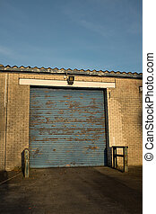 Loading bay. - A yellow brick building with a closed blue...