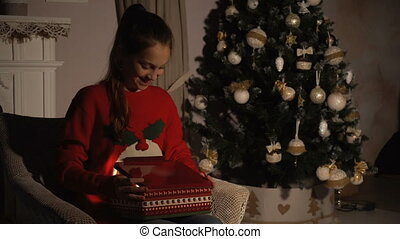 Beauty teen girl opening Christmas gift box with miracle lights