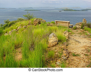 Hiking trail and a bench at the viewpoint on Kanawa Island in Flores Sea, Nusa Tenggara, Indonesia