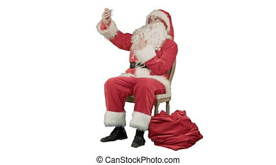 Santa makes selfie with smartphone on white background....