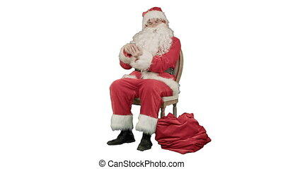 Santa laughing out loud as he talks on his cell phone on...