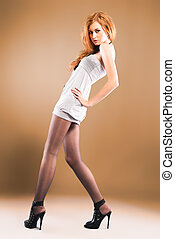 Attractive red-haired girl wearing beautiful dress and high heels shoes. Studio shot