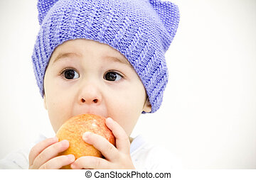 baby boy sitting on table with fruits and vegetables and eating an apple isolated on white background