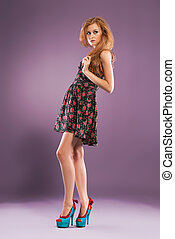 Beautiful red-haired girl on purple background/ Studio shot