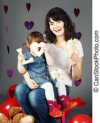 mother sitting on chair with baby girl toddler on her laps knees in studio holding wooden letters love