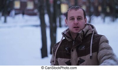 man throws a snowball at the camera