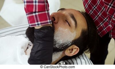 Barber applied to the face shaving foam by a swab. 4K