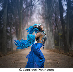 Freedom, Beautiful young woman with dress made of blue feathers, angel fallen from heaven to earth. Fantasy image and stories