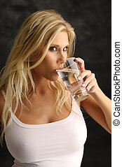 Blond girl with a glass of water in a white undershirt