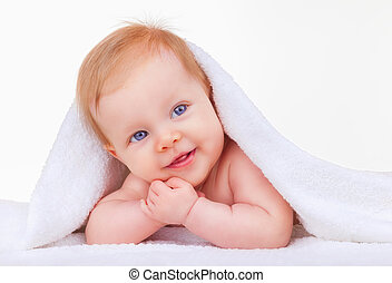 Infancy - Baby girl is hiding under the white blanket on a...