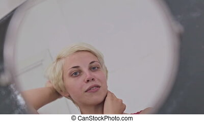 Sensual woman without make-up looking at her reflection in mirror, fixing hair