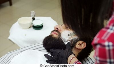 Barber shaves a white man with a straight razor - Barber...