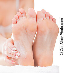 Chiropody - Close-up woman applying moisturizer cosmetic...