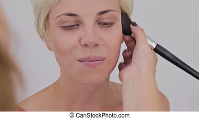 Close up shot. Professional make-up artist applying powder to woman s face